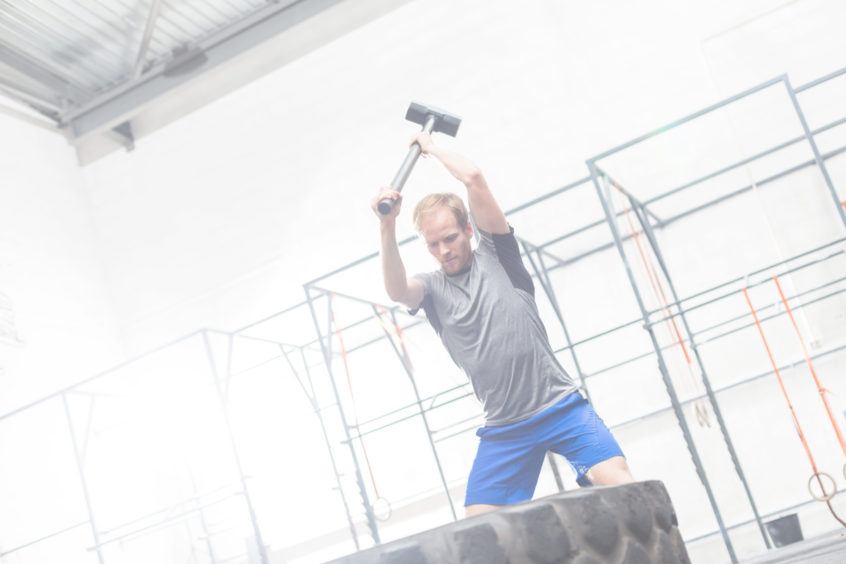 Man hitting tire with sledgehammer in crossfit gym